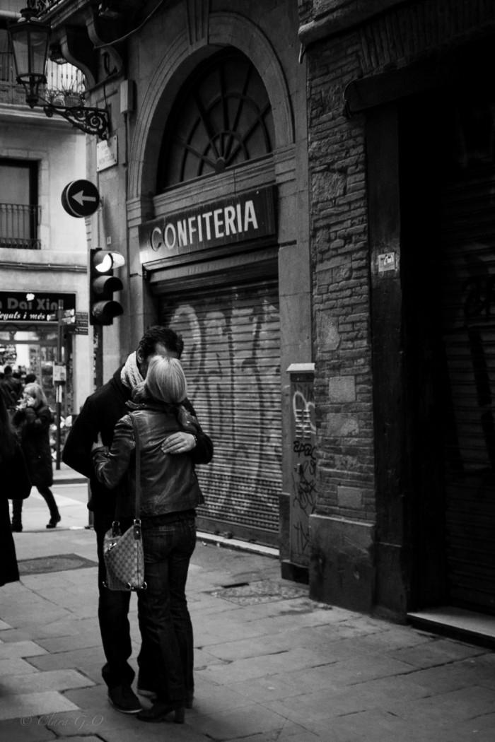 Parella fent-se un petó amb una confiteria de fons - © Clara .G.O